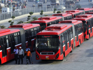 TO GO WITH Pakistan-unrest-vote-politics-development-education,FOCUS by Khurram Shahzad In this photograph taken on June 5, 2013, shows Pakistani employees walking beside metro buses parked at a terminal in the provincial capital Lahore. Pakistanis are hoping their new prime minister will roll out high-profile projects that became his party's trademark in its political heartland of Punjab, but the nation's dire finances threaten the optimism. The Pakistan Muslim League-N (PML-N) won huge popularity and a reputation for getting things done with a series of big-ticket schemes over the past five years in Punjab, the country's richest, most populous province. A metro bus system in the provincial capital Lahore -- the first such scheme in the country's 65-year history -- free laptops and solar energy panels for students and a network of high-quality schools in poor rural areas made Punjab the envy of Pakistan. AFP PHOTO / ARIF ALI